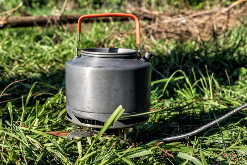 Tourist_boiling_kettle_at_the_stake_in_the_forest_at_sunset.jpg